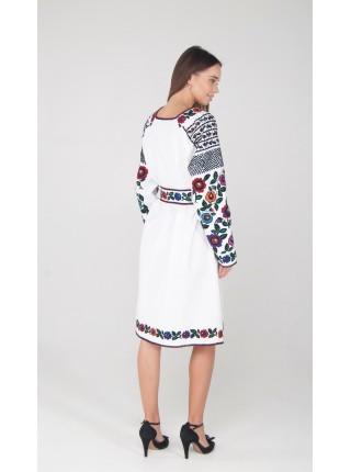 Біла сукня з вишитими яскравими квітами